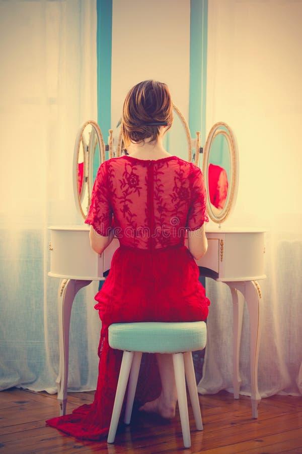 Jovem mulher perto do espelho do console fotos de stock