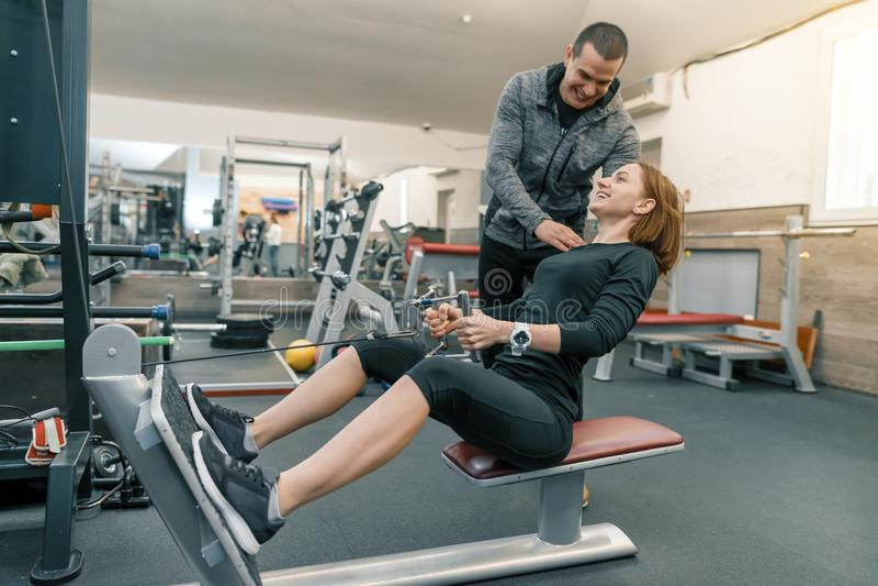 Jovem mulher pessoal do treinamento de instrutor da aptidão no gym Esporte, atleta, treinamento, estilo de vida saudável e concei imagens de stock