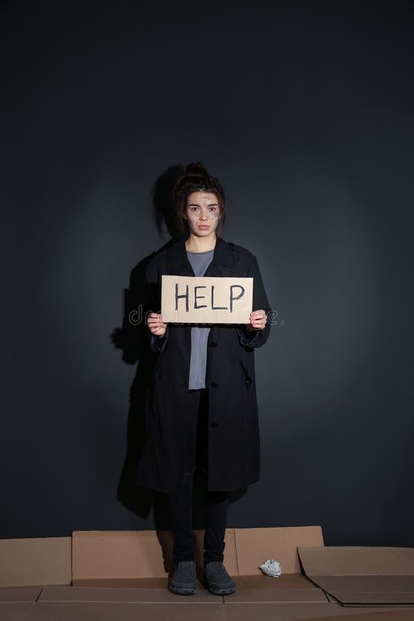 Jovem mulher pobre com posição do sinal da AJUDA perto da parede imagem de stock