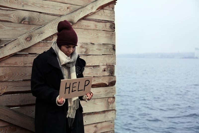 Jovem mulher pobre com sinal da AJUDA no beira-rio fotos de stock