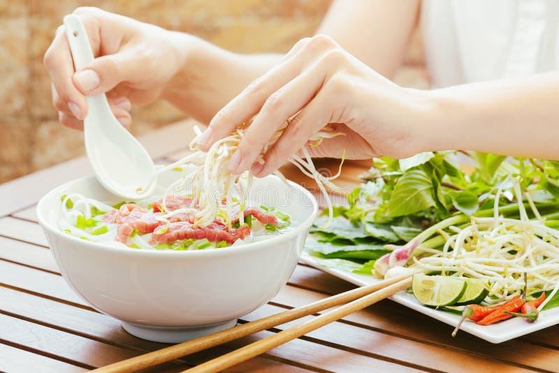 A jovem mulher polvilha brotos ao Pho BO no café vietnamiano fotos de stock