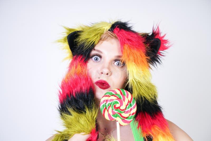 Jovem mulher positiva de encantamento do tamanho no chapéu forrado a pele feito de fibras coloridos com as orelhas e as patas de  fotos de stock