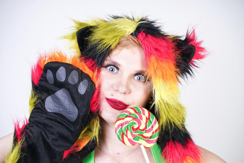 Jovem mulher positiva de encantamento do tamanho no chapéu forrado a pele feito de fibras coloridos com as orelhas e as patas de  fotografia de stock royalty free