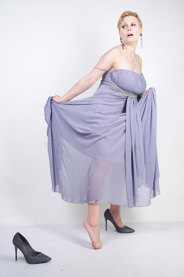 A jovem mulher positiva de encantamento do tamanho no vestido cinzento do vestido perdeu o deslizador no fundo branco no estúdio  imagem de stock