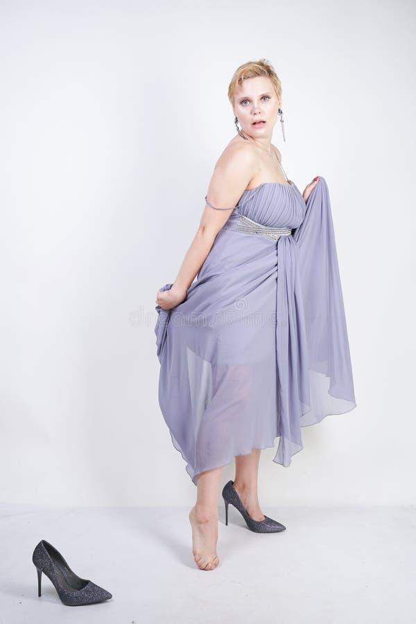 A jovem mulher positiva de encantamento do tamanho no vestido cinzento do vestido perdeu o deslizador no fundo branco no estúdio  fotos de stock royalty free