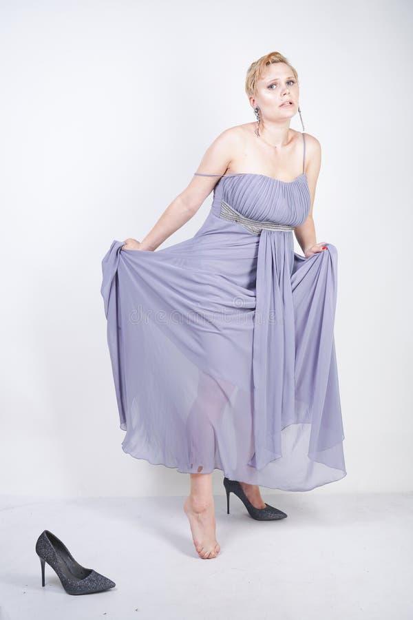A jovem mulher positiva de encantamento do tamanho no vestido cinzento do vestido perdeu o deslizador no fundo branco no estúdio  foto de stock royalty free