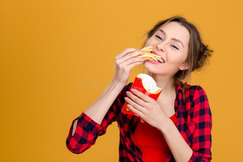 Jovem mulher positiva encantador na camisa quadriculado que come fritadas foto de stock royalty free
