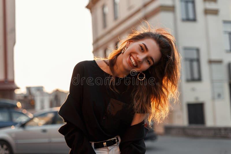 Jovem mulher positiva engra?ada na roupa preta ? moda que levanta e que sorri positivamente na cidade foto de stock royalty free