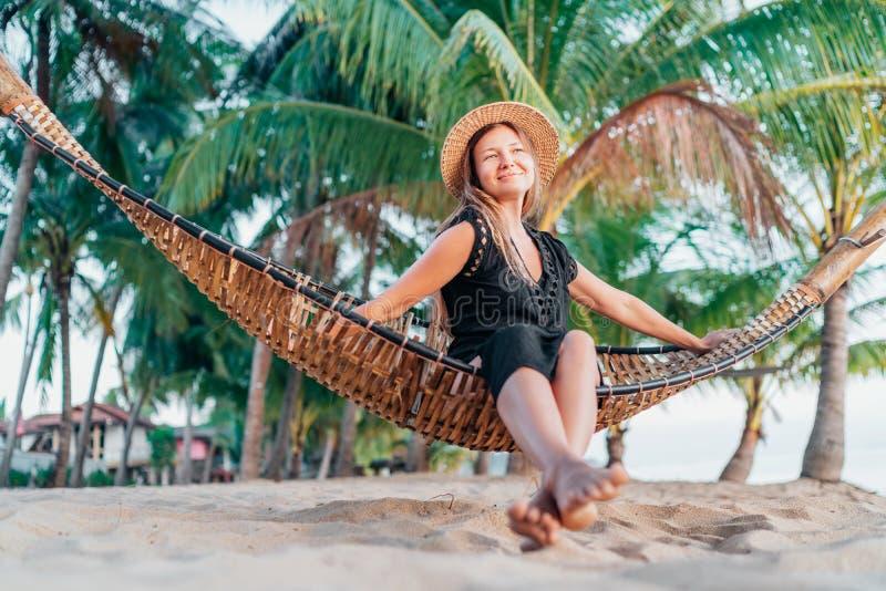 Jovem mulher positiva no chapéu de palha que balança na rede na praia tropical fotografia de stock royalty free