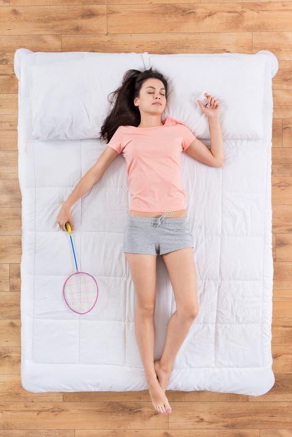 Jovem mulher positiva que encontra-se na cama imagens de stock