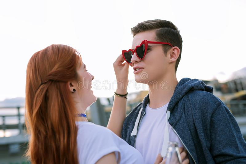 Jovem mulher positiva que põe óculos de sol sobre seu noivo imagens de stock royalty free