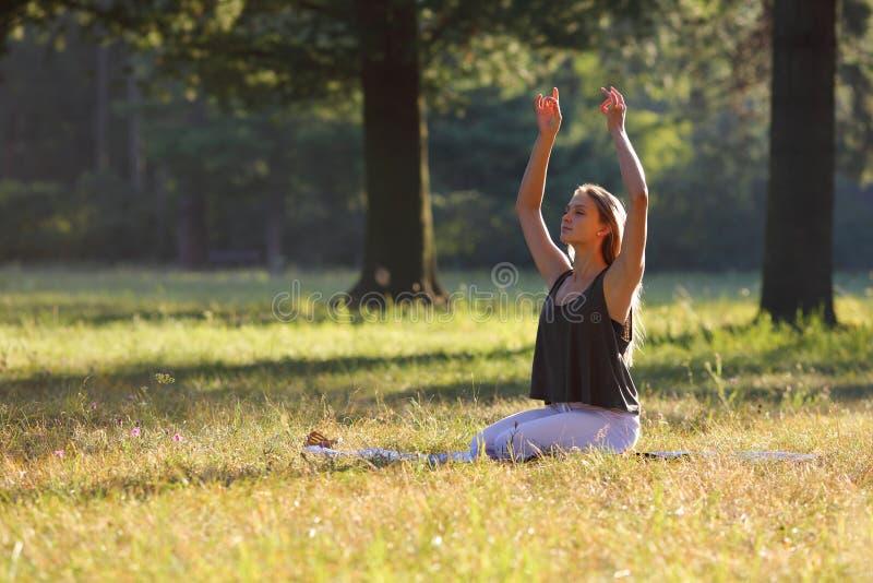 A jovem mulher pratica a ioga no parque imagem de stock royalty free