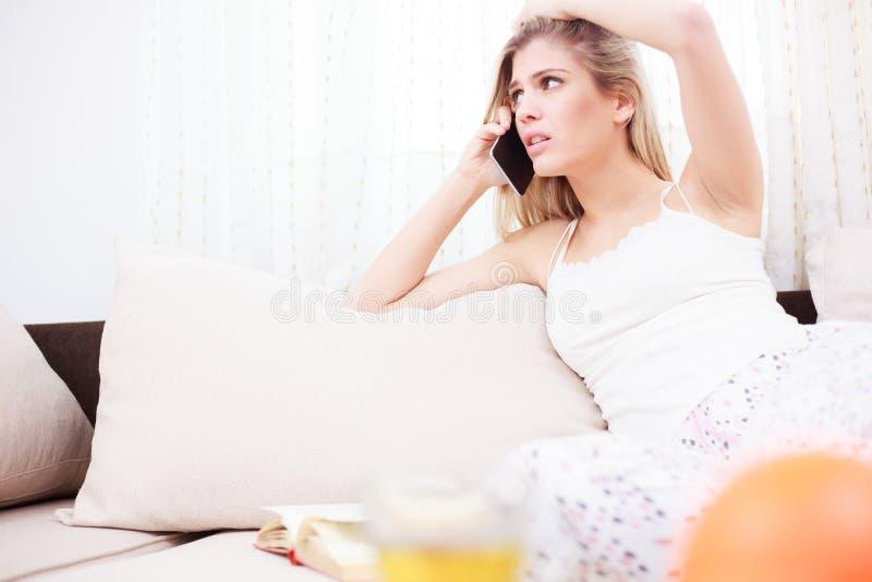 Jovem mulher preocupada bonita que fala no telefone foto de stock royalty free