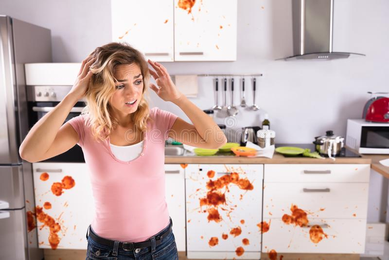 Jovem mulher preocupada que está na cozinha suja imagens de stock royalty free