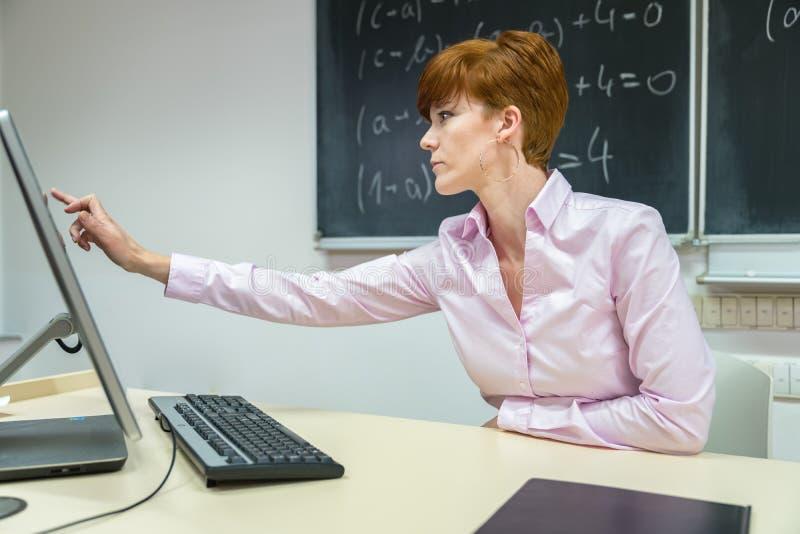 A jovem mulher prepara uma lição de ensino na classe em seu computador imagens de stock
