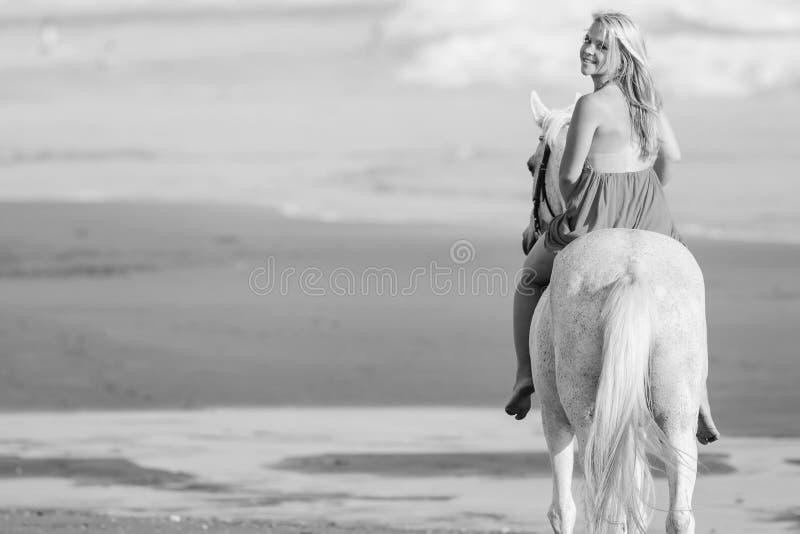Jovem mulher preto e branco da imagem que monta um cavalo fotografia de stock royalty free