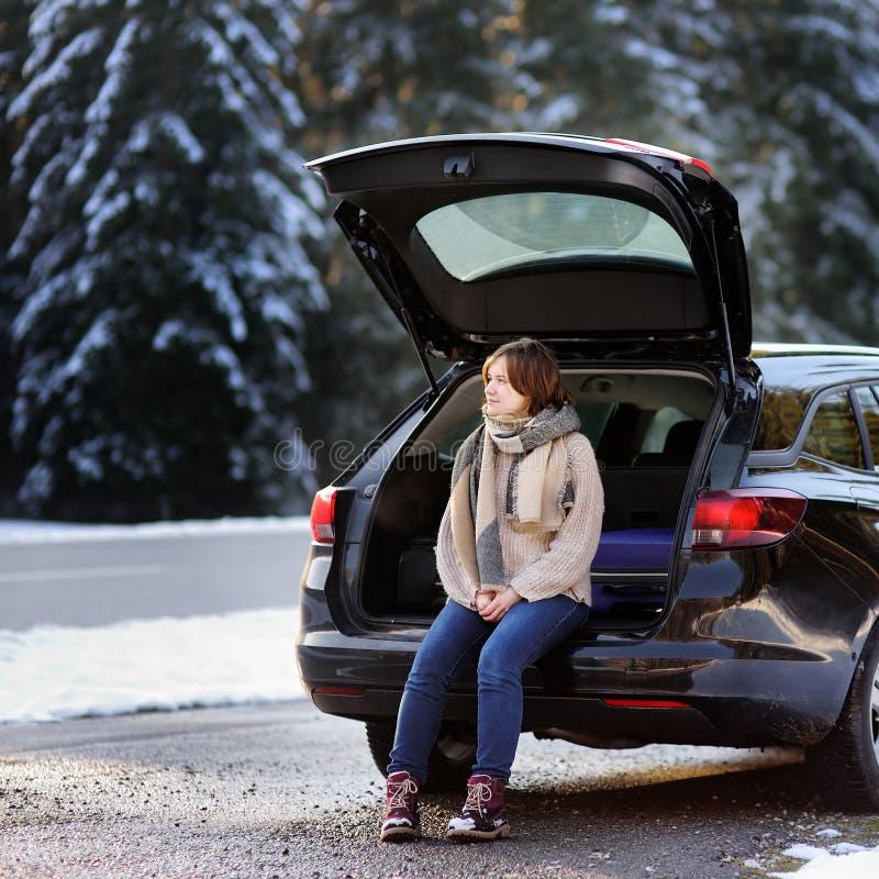 Jovem mulher pronta para ir em férias e no relaxamento no tronco aberto de um carro antes de uma viagem por estrada fotos de stock