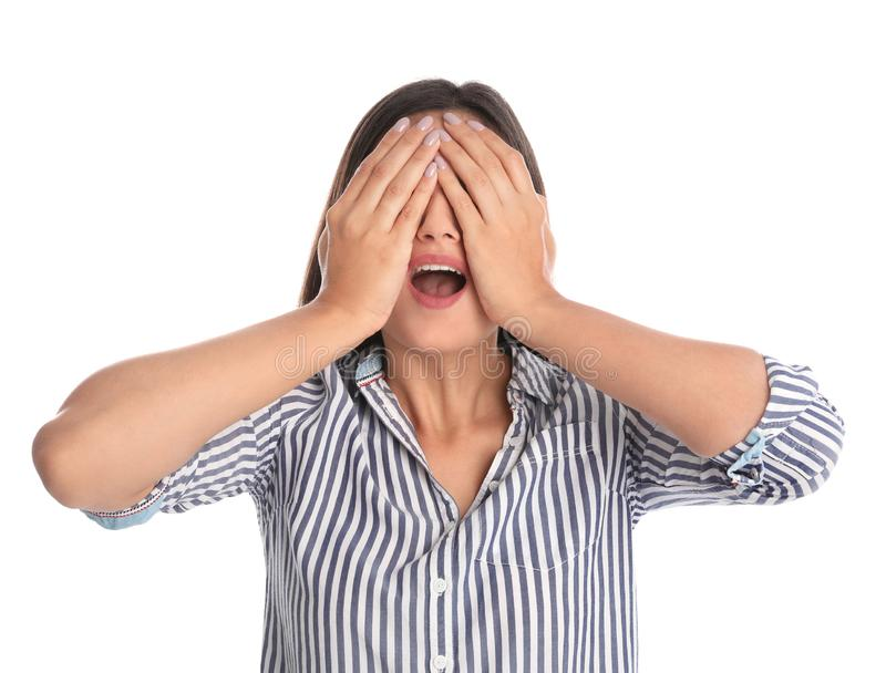 Jovem mulher que é cegada e que cobre os olhos com as mãos no branco foto de stock