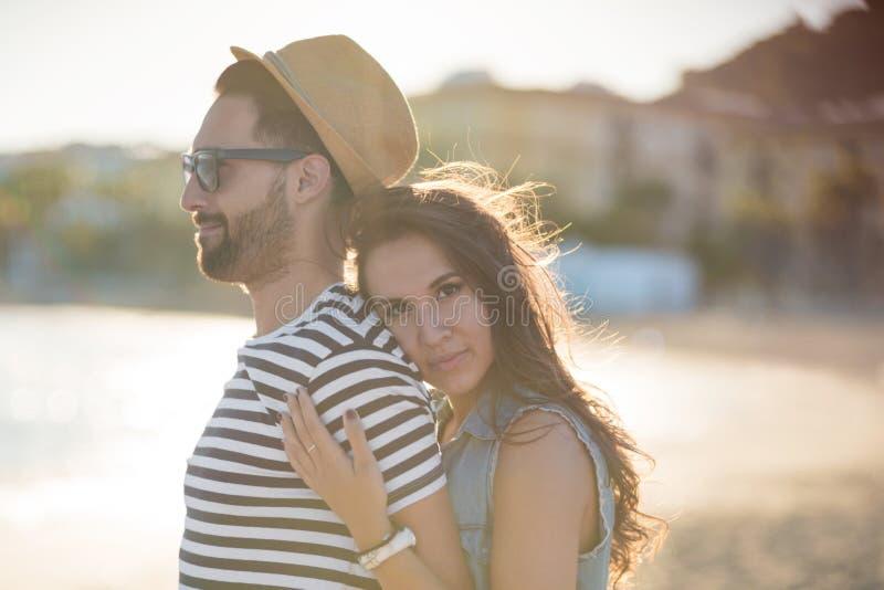 Jovem mulher que abraça seu noivo feliz no beira-mar imagens de stock