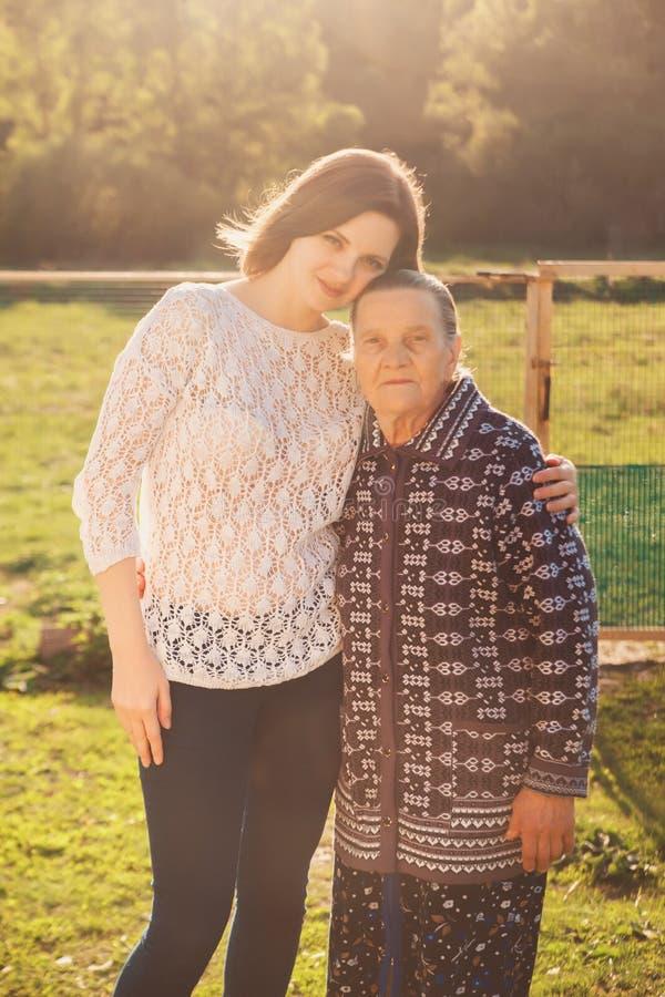 Jovem mulher que abraça uma avó fora foto de stock royalty free