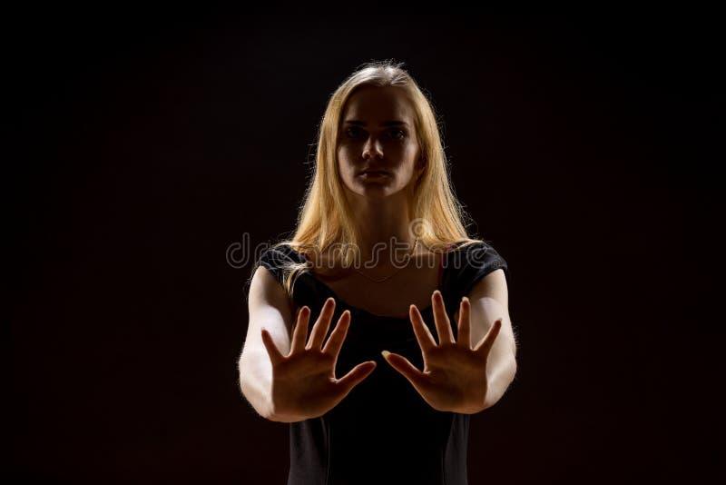 Jovem mulher que acena suas mãos Menina loura que expressa com mãos levantadas suas emoções em um estúdio em um fundo preto imagem de stock