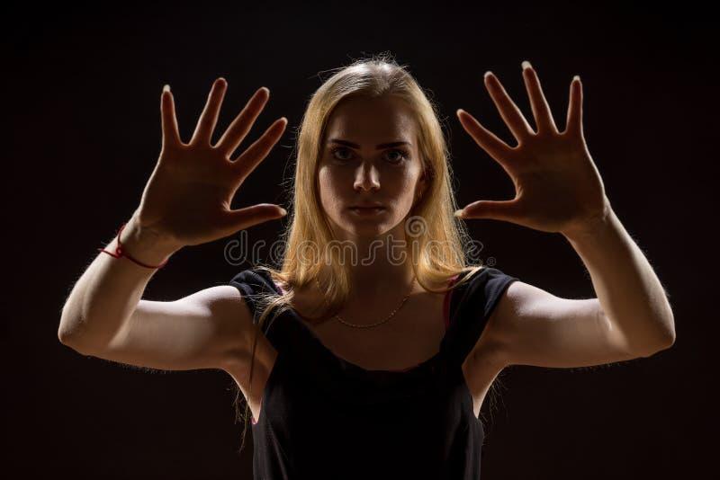 Jovem mulher que acena suas mãos Menina loura que expressa com mãos levantadas suas emoções em um estúdio em um fundo preto imagem de stock royalty free