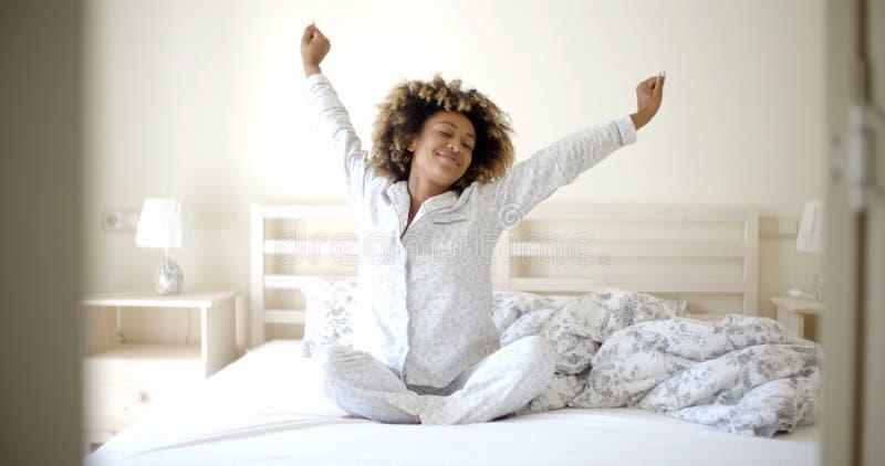 Jovem mulher que acorda na cama imagem de stock