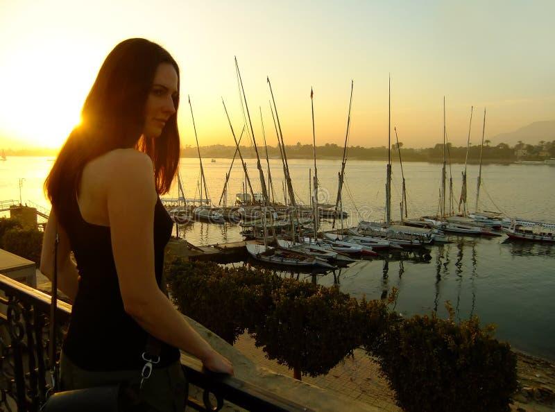 Jovem mulher que admira o por do sol sobre o Nile River, Luxor fotos de stock