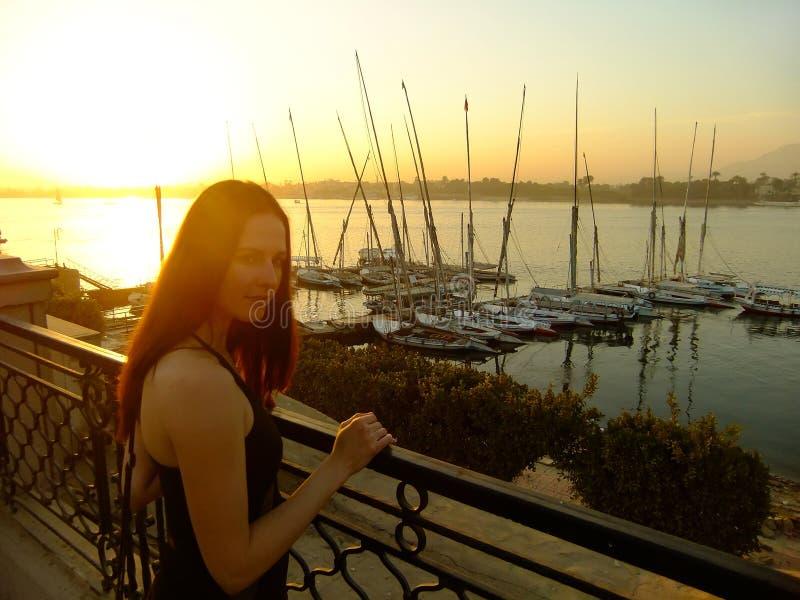 Jovem mulher que admira o por do sol sobre o Nile River, Luxor imagem de stock