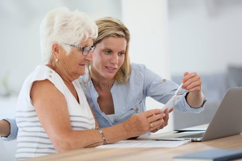 Jovem mulher que ajuda o smartphone de utilização idoso fotos de stock