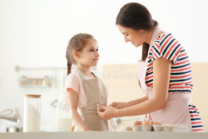 Jovem mulher que ajuda sua filha a pôr sobre o avental na cozinha Fazendo a massa junto fotografia de stock