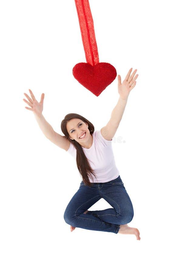 Jovem mulher que alcança para fora para o sorriso vermelho do coração fotos de stock