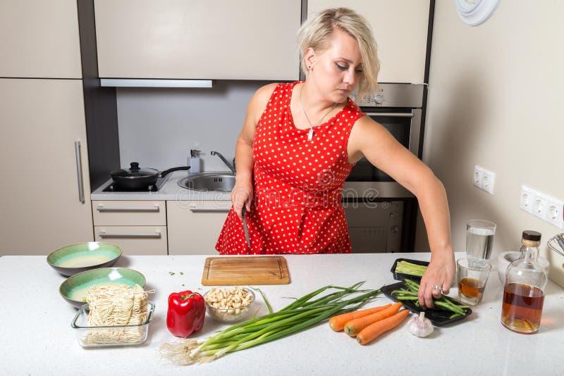 Jovem mulher que alcança para o aspargo e que guarda a faca no outro ha fotografia de stock