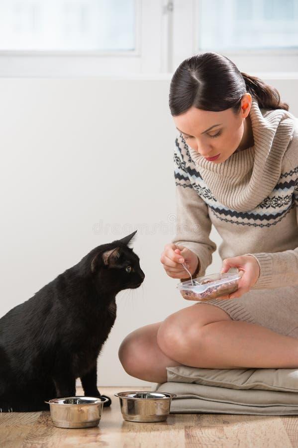 Jovem mulher que alimenta seu gato em casa foto de stock royalty free