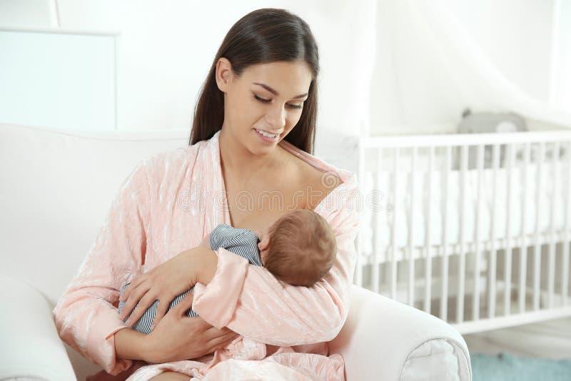 Jovem mulher que amamenta seu bebê no berçário imagem de stock