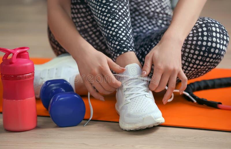 Jovem mulher que amarra laços no assoalho no gym, close up foto de stock
