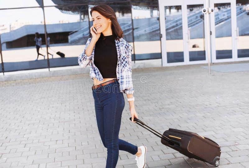 Jovem mulher que anda com mala de viagem da bagagem e smartphone de fala, férias, curso e conceito ativo do estilo de vida imagens de stock royalty free