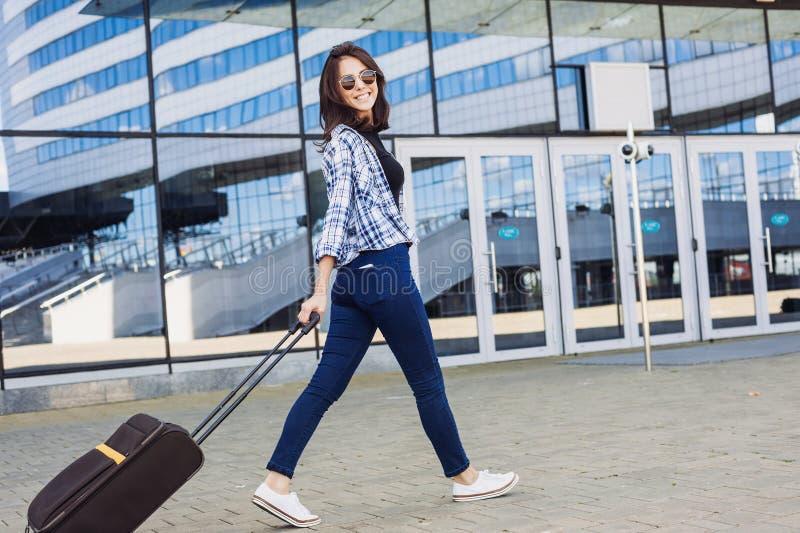 Jovem mulher que anda com mala de viagem da bagagem, f?rias, curso e conceito ativo do estilo de vida fotografia de stock
