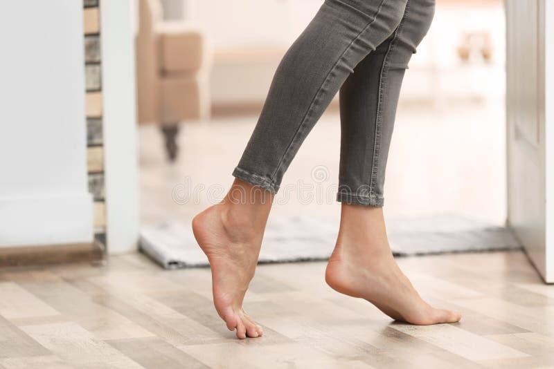 Jovem mulher que anda com os pés descalços em casa, close up fotografia de stock royalty free