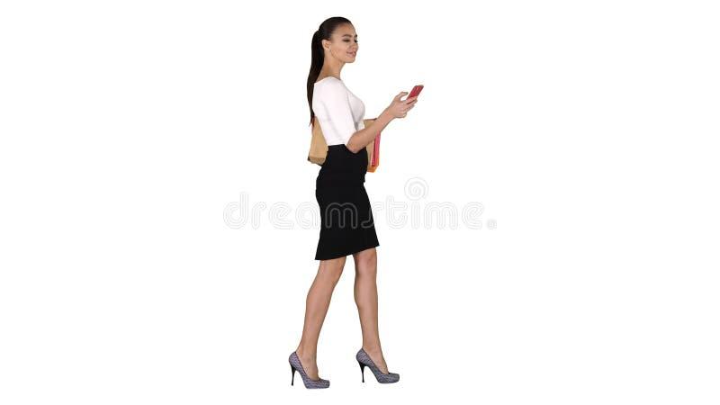 Jovem mulher que anda com os sacos de compras que falam no telefone celular no fundo branco fotos de stock
