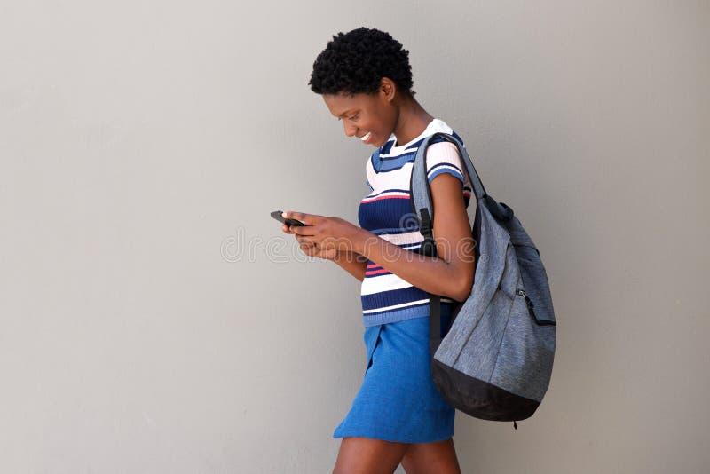 Jovem mulher que anda com saco e que usa o telefone esperto no fundo cinzento imagem de stock royalty free