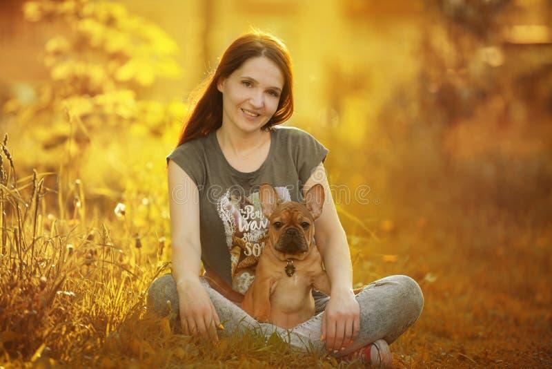 Jovem mulher que anda com um cachorrinho do buldogue francês imagem de stock royalty free