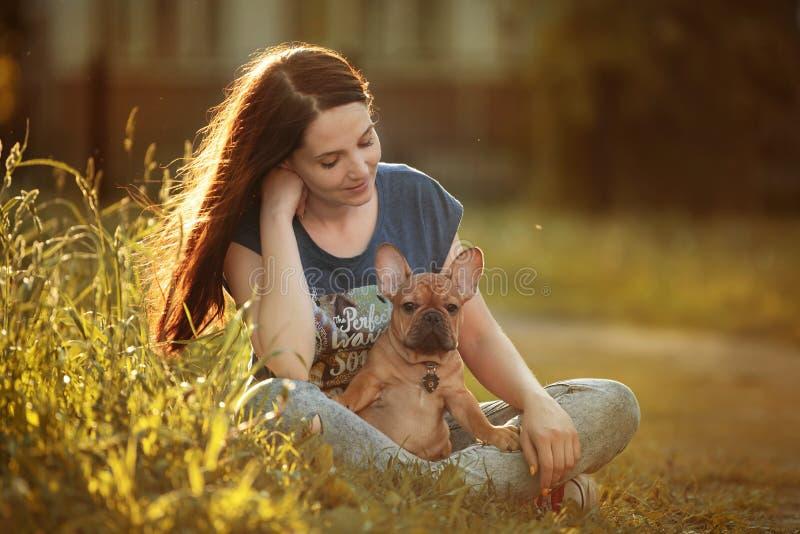 Jovem mulher que anda com um cachorrinho do buldogue francês imagem de stock