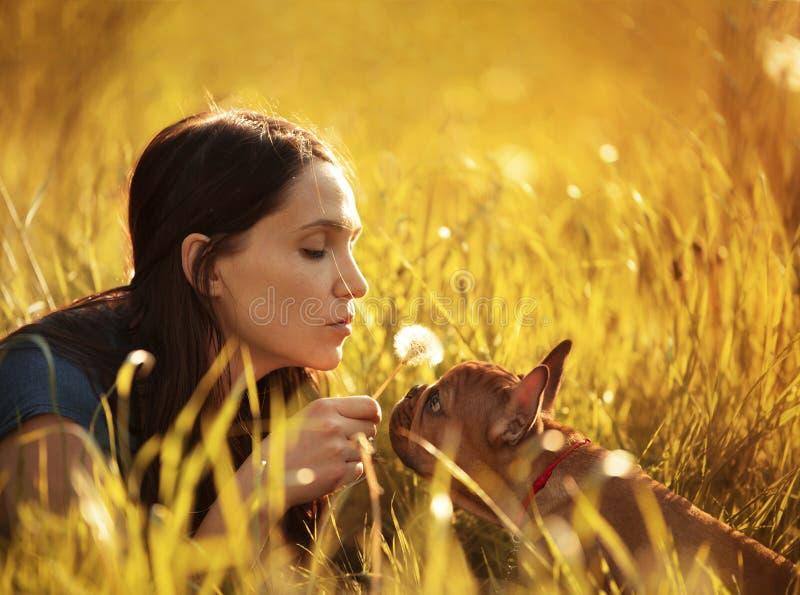 Jovem mulher que anda com um cachorrinho do buldogue francês foto de stock royalty free