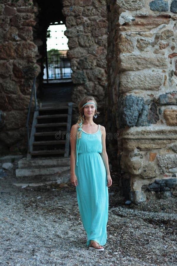 Jovem mulher que anda contra o fundo borrado da pedra medieval imagens de stock royalty free