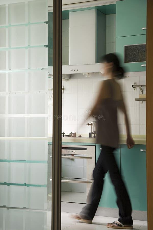 Jovem mulher que anda em uma cozinha fotos de stock royalty free