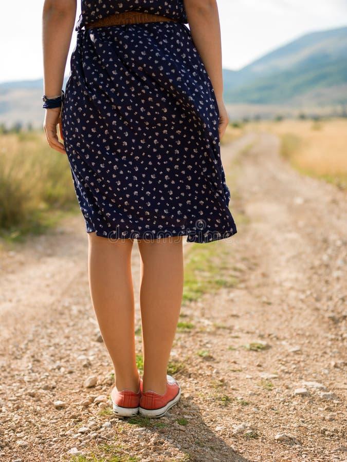 Jovem mulher que anda em uma estrada abandonada longa fotografia de stock