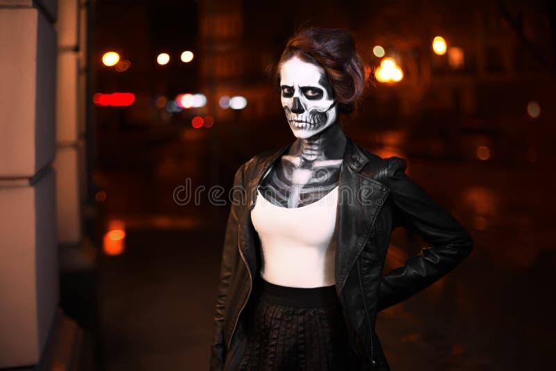 Jovem mulher que anda na avenida Arte da cara para o partido de Dia das Bruxas Retrato da rua Cintura acima Fundo da cidade da no imagem de stock royalty free