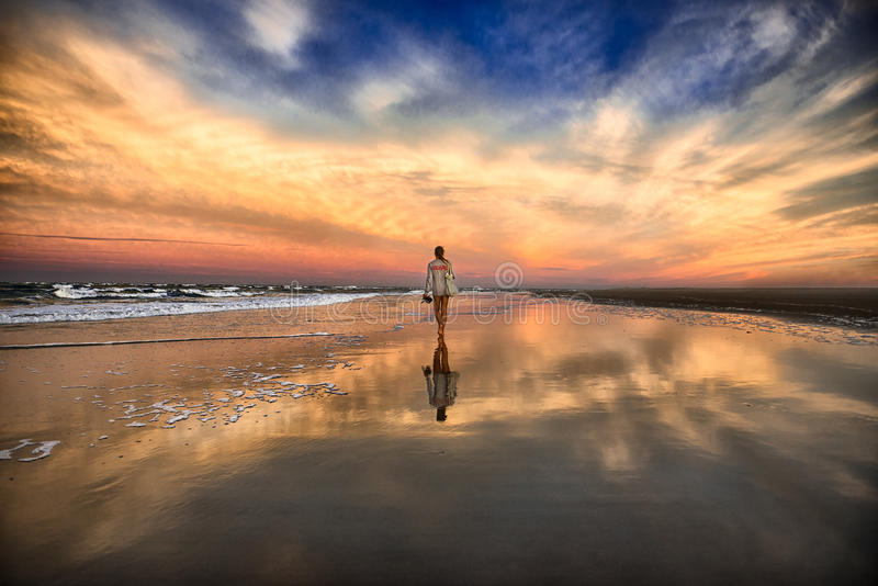 Jovem mulher que anda na praia perto do oceano e que anda afastado no por do sol imagem de stock royalty free