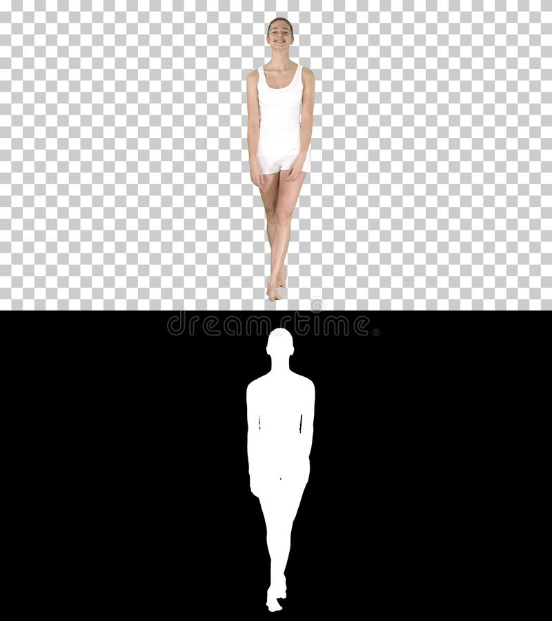 Jovem mulher que anda na roupa branca dos esportes com os pés descalços e que sorri extensamente, Alpha Channel foto de stock